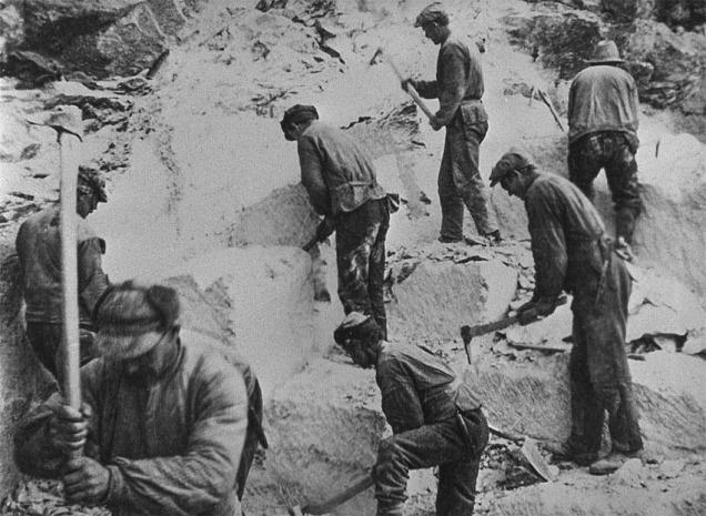 Dette er ikkje verken bundne gardsfolk eller trælar. Det er steinbrytarar som hogg kleberstein på det urgamle viset enno i 1932. På den tida var det elles vanleg å nytta boring og sprenging. Biletet visar korleis det kan ha sett ut i i eit steinbrot for 1000 år sida. Frå Vesleseterberget ved Otta. Kjelde: Maihaugen, Lillehammer.