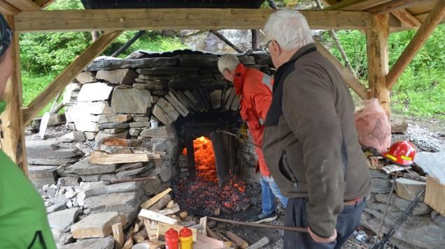 Torbjørn og Sveinung jobber tungt med å mate kalkovnen med god ved under vår første brenning i juni 2017. Foto: Per Storemyr