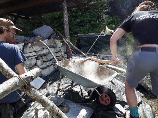 Blanding av hotmix, lesking av kalk i sand på plassen. Vert god mørtel for ombygginga av kalkovnen. Det er hett! Lesking av kalk gjer stor varme. George Murhy og Bjørn Idland frå Stavanger i aksjon.