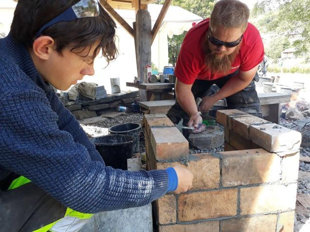 Tore Granmo og Jakob Solheim bygger brennkammeret på Miniovnen i juni 2018.
