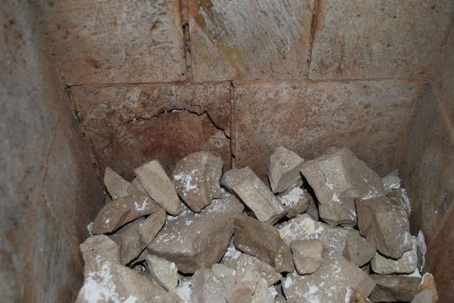 Skjellene er tatt ut og de brente marmorbitene under kommer til syne. Legg merke til sprekker i kleberforingen.