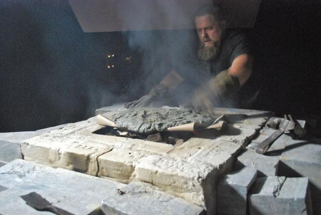 Tore Granmo legger på et lokk av kalkforsterket leiremørtel for å «holde på varmen» i ovnen. Dette er en velprøvd metode med mulige aner allerede i romertiden. Papiret brenner opp! Det gjorde også greiner og bregner, som også ble brukt til å legge leiremørtelen på
