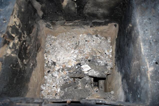 Pakkende skjellgrus over det nedre laget med marmor. Vi har tatt vekk et par marmorbiter for å bedre kunne bedømme tilstanden. Legg merke til at ovnen er sotet. Det er et sikkert tegn på at temperaturene ikke har vært høye nok.