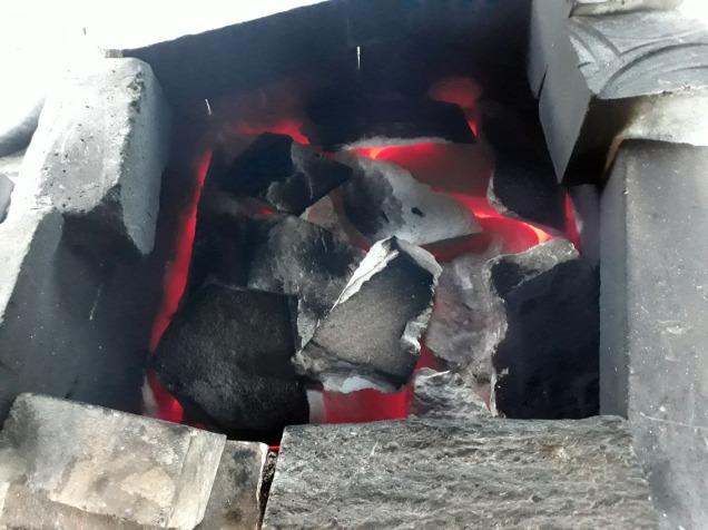 """Små marmorplater på toppen av ladningen som brennes. De holder på varmen i ovnen. Rundt er det satt opp opp stein som fungerer som en liten """"pipe"""""""