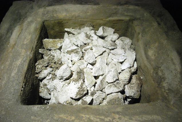 """Den ferdig brente marmoren etter fjerning av topplokket. Hvit og fin! (brun """"sand"""" er fra pulverisert kalkmørtel fra topplokket)"""
