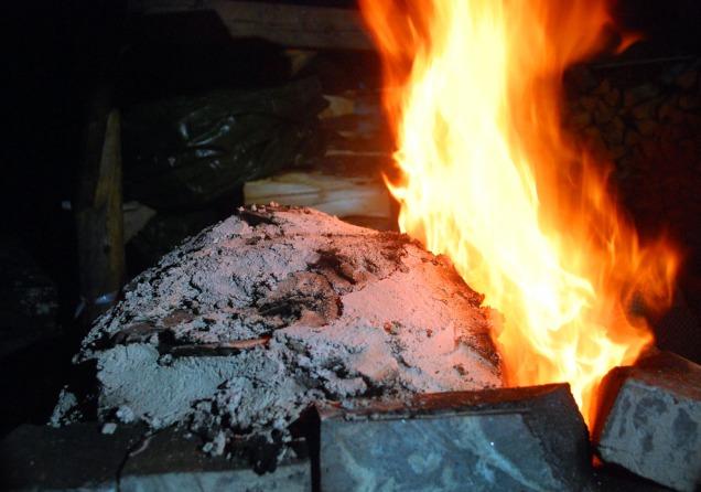 Marmorlokk murt med kalkmørtel ferdig. Flammene slår voldsomt opp foran i ovnen