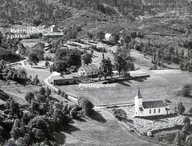 Prestegarden og Hyllestad kyrkje, med utsyn mot Kvernsteinsparken, der det under 2. verdskrigen var hus og brakker. Foto: Telemark flyveselskap, 1956