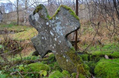 Ein av steinkrossane frå mellomalderen i hjørna på muren kring kyrkjegarden. Foto: Per Storemyr