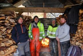 Arbeidslaget ved den første brenningen, foran kalkovnen, med ved på alle kanter, f. v.: Kjetil Monstad, Haakon Aase, Berit Bruvik og Tore Granmo