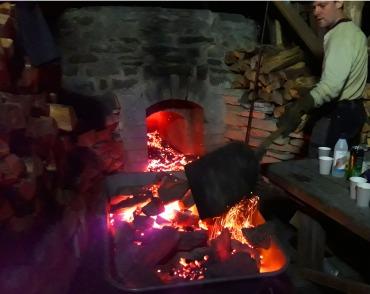 Nedfalte stein og glødende kull spas ut av ovnen etter at brenningen er erklært ferdig. Midt på natten.