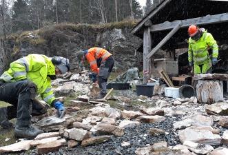 Berit Bruvik, Kjetil Monstad og Haakon Aase bearbeider marmorheller som skal brukes til brennkammerhvelv i kalkovnen.
