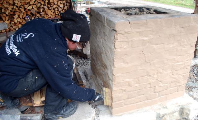 Sverre slemmer ovnen med beige Hyllestadkalk mens vi småfyrer for å tørke hvite Skaftåkalk til brenning.