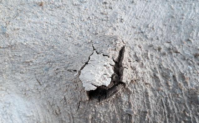 """Kalksprett! En bit brentkalk er ikke godt nok lesket under blanding. Så lesker den på muren. Igen fare. Biten tas ut og det skadde området """"trykkes inn""""."""